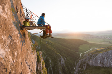 two climbers watching the sunset from their portaledge