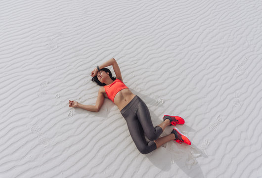 Exhausted athletic girl lying on the ground after a workout