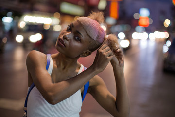 Young woman fixing her hair on the street