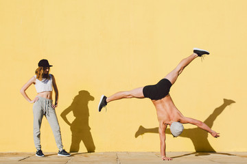 Couple doing acrobatics in front of a yellow wall.