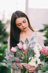 Long-haired brunette girl holds a flwers bouquet