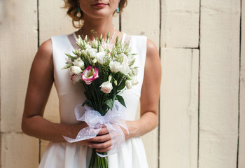 Pretty stylish sensual woman posing on the street in wedding dress with flowers