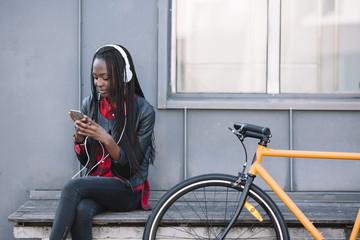 Smiling female in headphones using smartphone