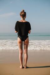 Beautiful tatooed woman on the beach in summer
