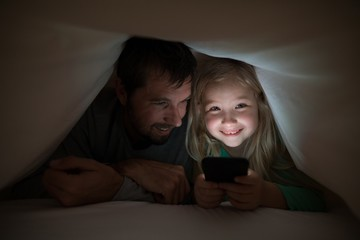 Father and daughter lying under blanket and using mobilephone