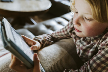 Young girl playing games on tablet