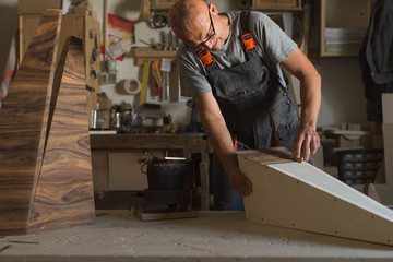 Carpenter sticking a piece of veneer to a wooden surface