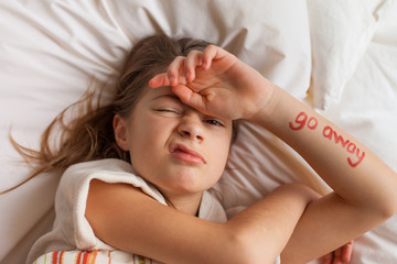 Tween girl with grumpy expression and the words 'go away' written on her arm