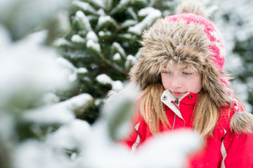 Little Girl in Winter Snowy Christmas Tree Farm
