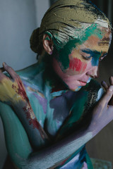 Closeup portrait of a young woman with colorful make-up and bodyart