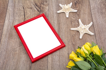 Red photo frame and yellow roses on a table