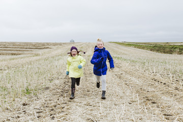 Young girls running together in farmers field