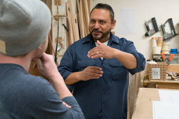 Middle aged hispanic blue collar worker gestures while talking t