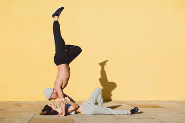 Couple in love doing acrobatics in front of a yellow wall.