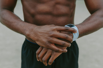 Unrecognizable Black Man Using a Activity Tracker Watch . Close up