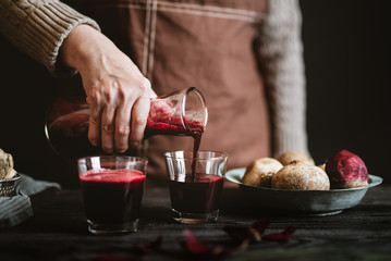 Woman serving freshly made beet and ginger juice