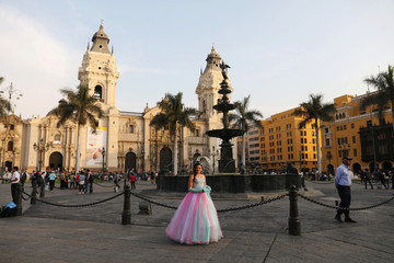 A girl celebrating her 15th birthday poses for a picture near the Government Palace in Lima
