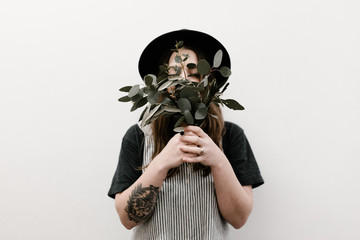 young woman with tattoo holding greenery in front of face