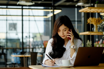 Portrait of an attractive young woman holding her phone while working in coffee shop.