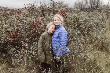 Outdoor portrait of young sisters in field of berries