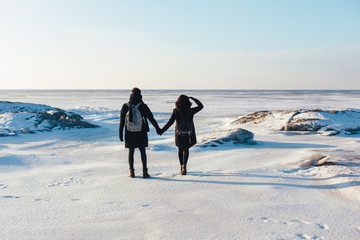 Young pretty couple posing in arctic background, freezing and have fun