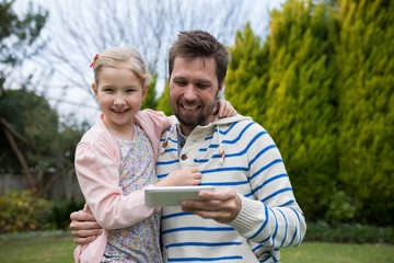 Young girl and father using digital tablet