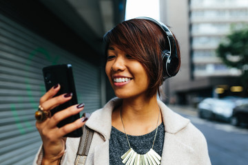 Young Businesswoman listening music on the Street with Headphones. Technology
