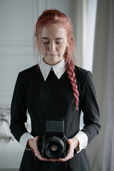 beautiful red-haired girl with vintage camera at home