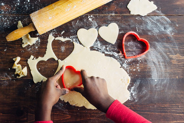 Black girl's hand cutting heart shaped cookies