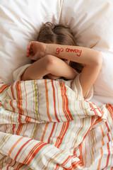 Tween girl with 'go away' message on her arm