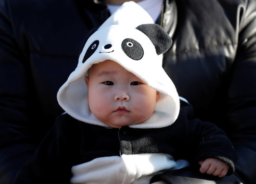 6-month-old baby Miu Suwazono wearing a costume featuring giant panda waits for starting the public debut of female baby panda Xiang Xiang at Ueno Zoological Gardens