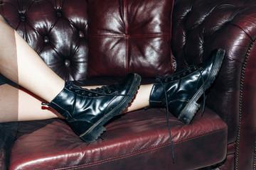 Black leather women shoes lying on luxury sofa