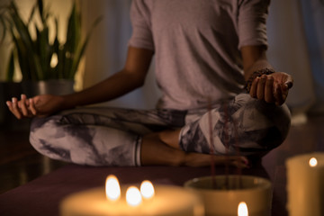 Woman meditating in candle-lit apartment