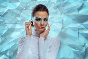 An attractive brunette model in futuristic office with virtual holographic glasses