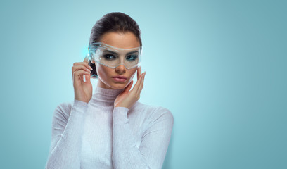 An attractive brunette model in futuristic office with virtual holographic glasses, smooth background with copyspace.