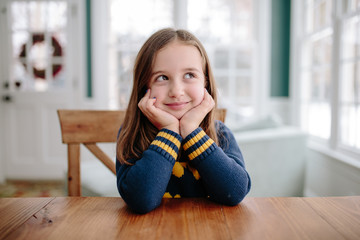 Cute young girl smiling at table