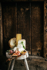 Cheese, salami and ham on wooden plate
