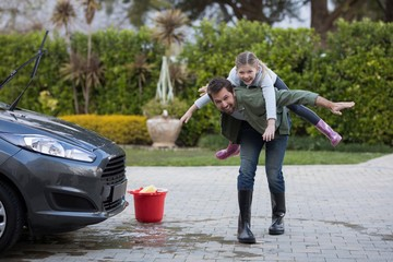 Teenage girl and father washing a car