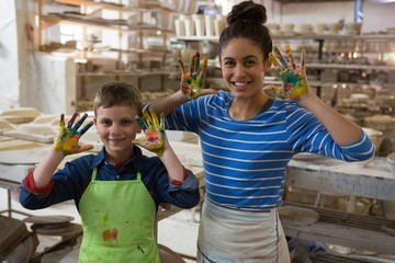 Mother and son showing colorful paint on their hands