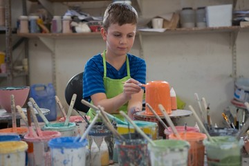 Boy painting a bowl in pottery shop