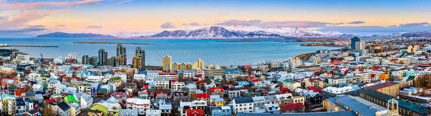Aerial panorama of downtown Reykjavik at sunset with colorful houses and snowy mountains in the background Wall mural