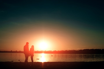 Silhouettes of a loving couple, beautiful sunset on a lake