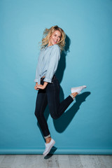 Full length image of Cheerful blonde woman in shirt jumping