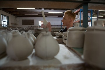 Male potter examining a earthenware equipment