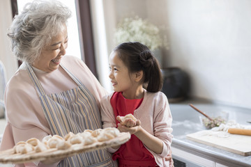 Cheerful granddaughter and grandmother making dumplings in kitchen