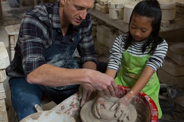 Male potter assisting girl in molding a clay