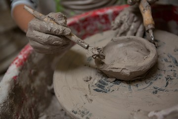 Close-up of girl molding a clay with hand tool