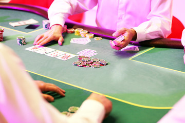 Games in the casino dealer deals cards and chips to players on the green table