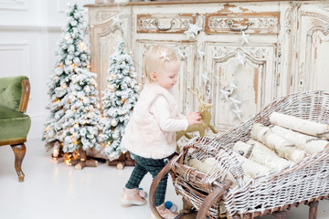 portrait beautiful little girl near old vintage chest of drawers. Christmas tree decoration and light bulbs garlands