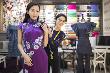 Fashion designer adjusting customer's dress